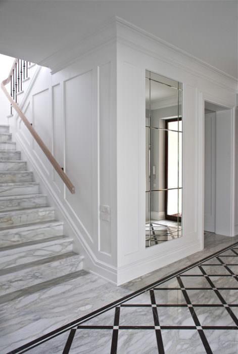 boazeria na klace schodowej połączona z boazerią ścienną w pisanym w niej lustrem