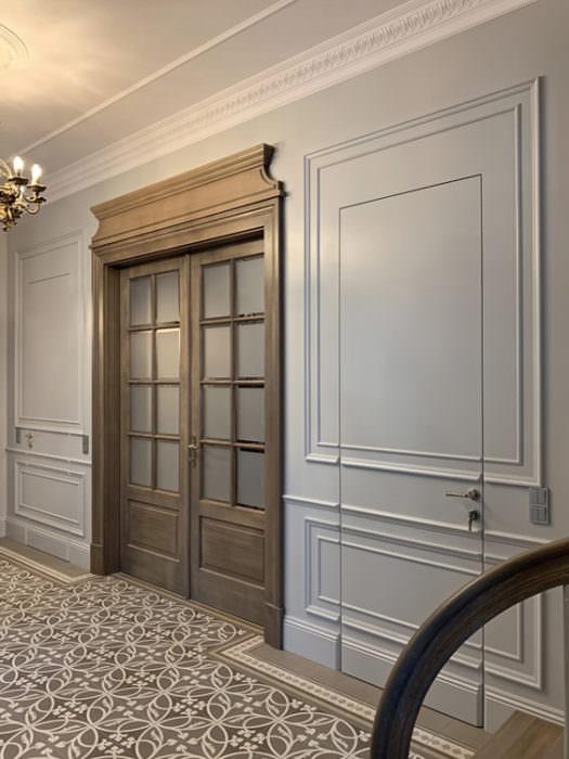 Efektowny zestaw drzwi przeszklonych i pełnych. Drzwi gładkie zdobione listwami sztukaterii otwierają się w jednym przypadku na korytarz, w drugim w kierunku przeciwnym